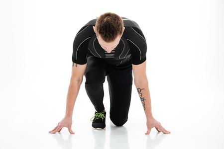 koncentrovaný: Portrét mladého soustředěného mužského sprinter připravuje začít běh izolovaných na bílém pozadí Reklamní fotografie