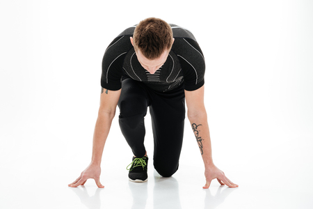 concentrated: Portrait of a young concentrated male sprinter preparing to start running isolated over white background Stock Photo