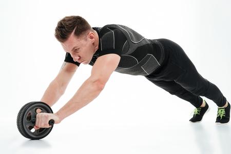 흰색 배경 위에 절연 피트 니스 롤러 장비와 운동을 하 고 근육 건강 한 선수 남자의 전체 길이 초상화