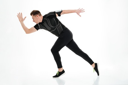 Side view full length portrait of a healthy sportsman started to run isolated over white background Standard-Bild