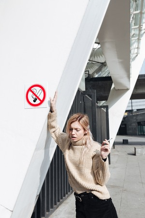 looking aside: Fashion portrait of serious young blonde lady with cigarette outdoors. Looking aside. Stock Photo