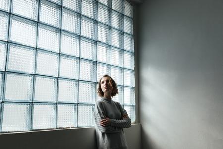 접힌 손으로 창이 근처 sportsuit 서 입고 젊은 여자