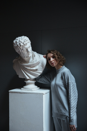 Young woman with curly hair wearing sportsuit standing near bust in museum Stock fotó