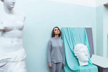 Young woman standing against a wall between statue and a bust in a classroom