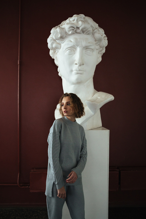 Young confident woman with curly hair standing and leaning on bust in museum. Looking aside