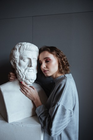 Close up of a young woman leaning on a marble bust in an art gallery
