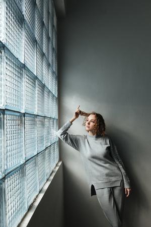 젊은 심각한 여자 회색 벽 근처 서있는 동안 창에서 찾고 스톡 콘텐츠