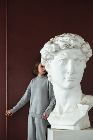 Young woman with curly hair and in sportsuit hiding behind the bust in museum