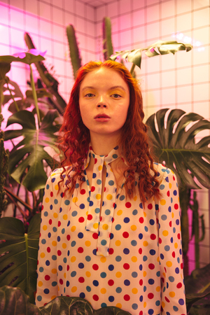 Fashion portrait of serious young redhead curly lady standing in cafe near latrine and plants. Looking at camera. Stock Photo