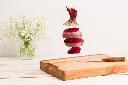 Sliced whole beetroot flying above a wooden chopping board with a knife