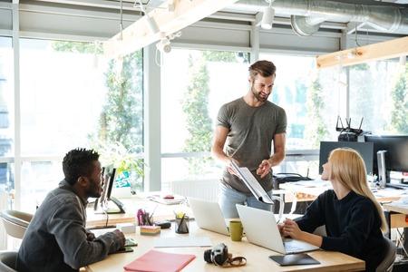 랩톱 컴퓨터를 사용 하여 office coworking에 앉아 웃는 젊은 동료의 이미지와 diagrama와 함께 작업합니다. 옆으로보고.