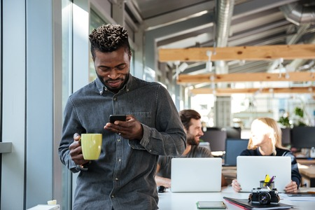 looking aside: Image of smiling young african man standing in office chatting by phone drinking coffee. Looking aside. Stock Photo