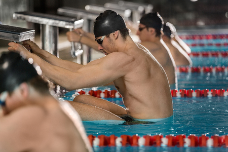 Male swimmers holding their starting blocks about to begin a back stroke race Stock Photo