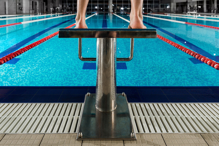 Mans feet standing on the starting blocks infront of swimming lane at a pool
