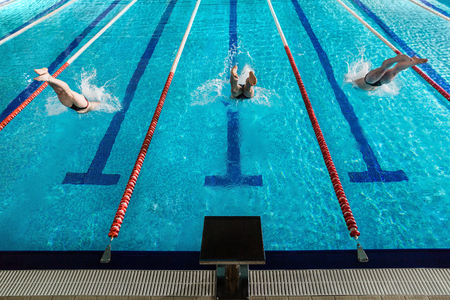 Rear view of three male swimmers diving into a swimming pool
