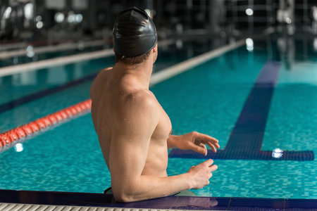 Rear view of a male swimmer standing at the edge of a swimming pool Stock Photo
