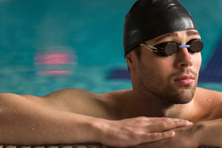 Cropped image of a male swimmer wearing goggles and swimming cap resting on the edge of a swimming pool Stock Photo