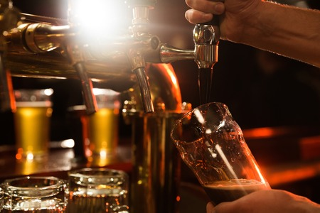 Close up of a bartender pouring beer while standing at the bar counter 스톡 콘텐츠