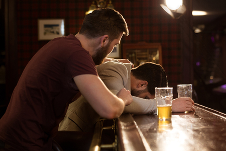 Young man helping his drunk sleeping friend at the counter in a pub or bar