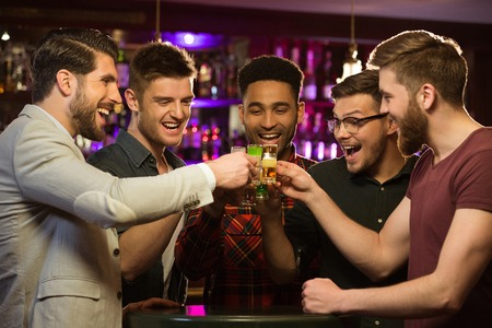 Happy male friends drinking beer and clinking glasses at bar or pub Imagens - 81430604