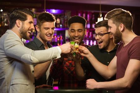 Amigos varones felices bebiendo cerveza y tintineo de vasos en el bar o pub