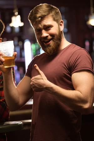 Gelukkige jonge bebaarde man die duimen laat zien en biertje in de lokale pub geniet