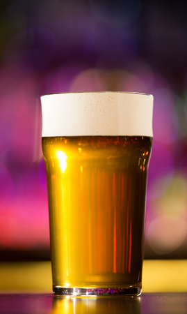 frothy: Close up of a beer glass standing on the bar counter Stock Photo