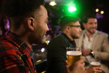 パブで友人とビールを持つ若い笑顔アフロ ・ アメリカ人