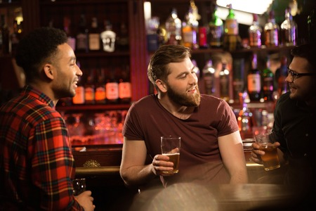 Smiling young men drinking beer, talking and smiling while resting at the pub photo