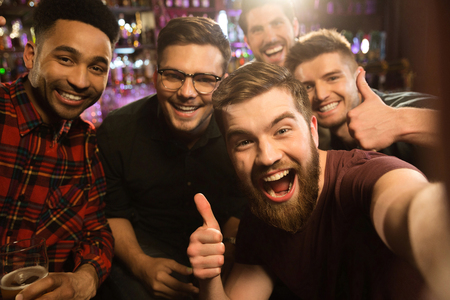 Cheerful old friends having fun by taking selfie and drinking draft beer in pub photo