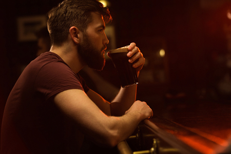 Side view of a young bearded man drinking glass of beer while sitting at the counter in pub or bar Stok Fotoğraf