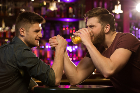 Two friends drinking beer and having fun at the pub or bar photo