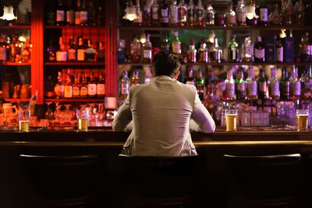 Back view of a young man drinking beer while while waiting for his friends at the bar counter Banco de Imagens