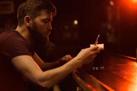 Young bearded man using mobile phone while having beer at a bar counter photo
