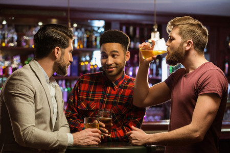 Happy laughing male friends catching up over pints in a bar photo