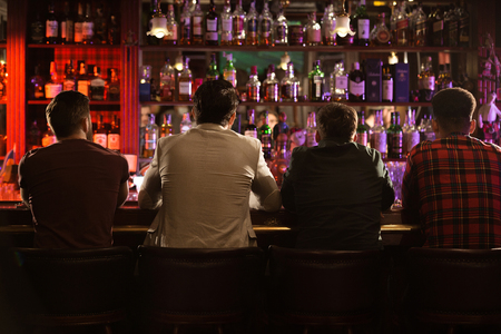 Back view of four young men drinking beer and talking while sitting at bar counter in a modern urban cafe