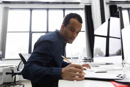 彼の机に座ってノートを作ってアフロ ・ アメリカ人のビジネスマン 写真素材