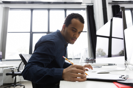 Afro american business man making notes while sitting at his desk Stock Photo