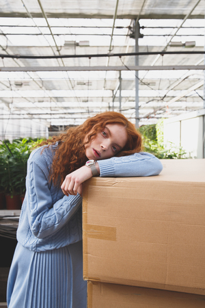 Portrait of serious cute girl lying on boxes near pots with plants in greenhouse