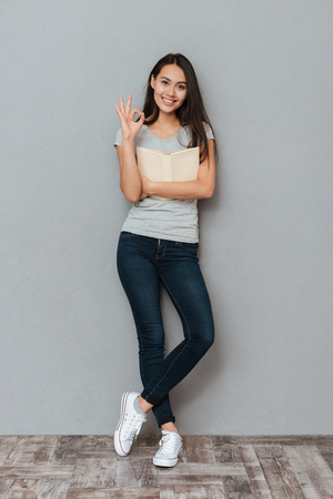 Full length of smiling cute young woman holding book and showing ok gesture over grey background