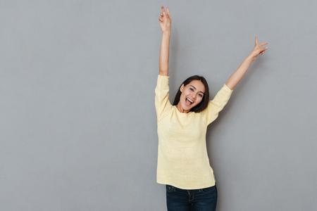 Happy joyful young woman with raised hands shouting and having fun over grey background Stock Photo