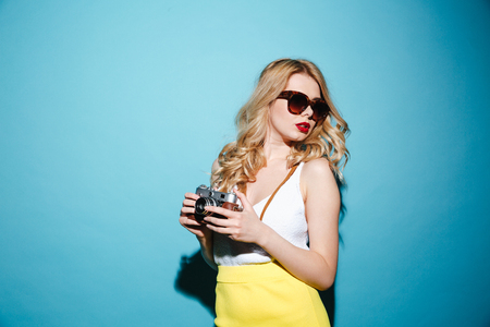 Portrait of a young stylish blonde woman in sunglasses holding retro camera isolated over blue background