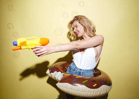 Portrait of a happy cheerful woman in summer clothes having fun with water gun isolated over yellow background