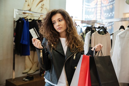 Image of sad curly young lady standing in women's clothing shop with shopping bags holding debit card. Looking aside. Zdjęcie Seryjne - 81572131
