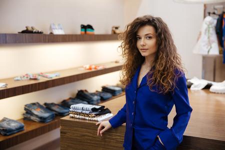 女性の衣料品店に立っているとポーズ、カメラを見て驚くべきの中の若い女性のイメージ。