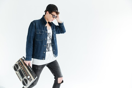 Picture of attractive young man wearing glasses standing isolated over white background and holding boombox. Looking aside.