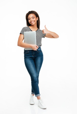 Full length portrait of a cheerful african teenager girl holding laptop and showing thumbs up gesture isolated over white background 版權商用圖片