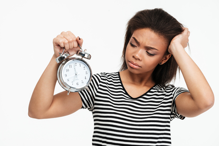Portrait of an upset frustrated african girl looking at alarm clock isolated over white background Stock Photo