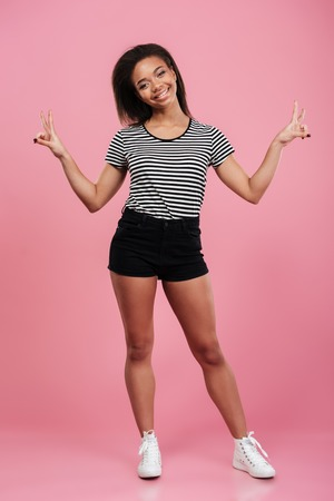 Full length portrait of a smiling young afro american woman standing and showing peace gesture with two hands isolated over pink background