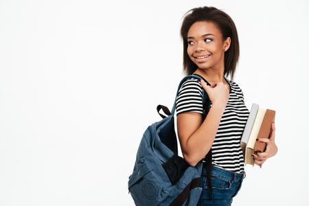 Portret van een glimlachend Afrikaans tienermeisje die rugzak dragen en weg kijken die over witte achtergrond wordt geïsoleerd Stockfoto